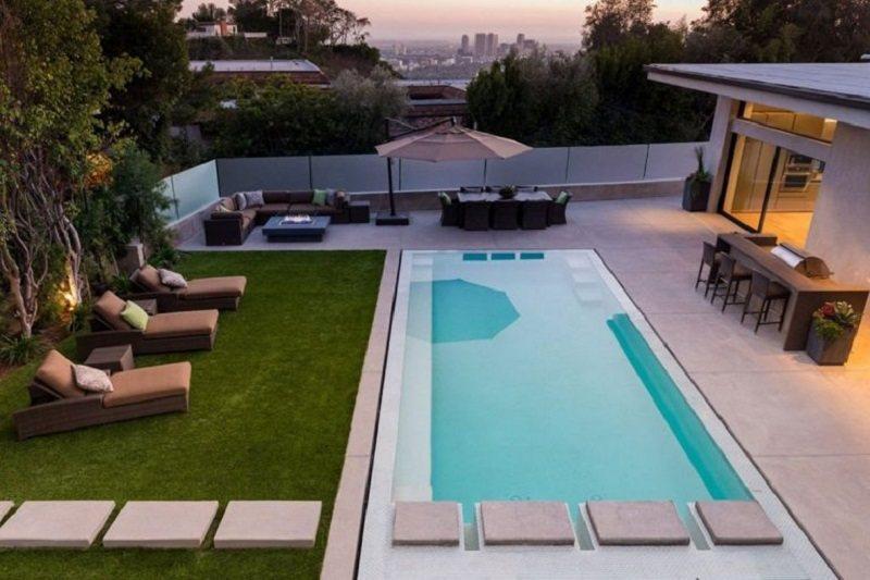Một bãi cỏ xanh ngay bên cạnh một bể bơi càng giúp không gian tươi mát hơn